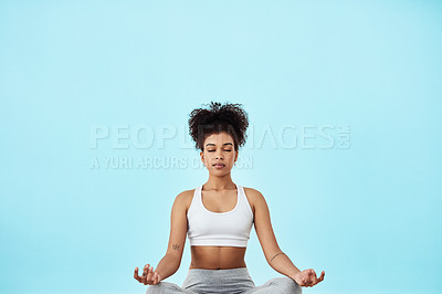 Buy stock photo Studio shot of a fit young woman meditating against a blue background