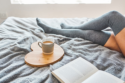 Buy stock photo Shot of an unrecognizable woman sitting next to her coffee and a book