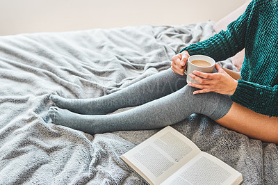 Buy stock photo Cropped shot of an unrecognizable woman having coffee while sitting next to her book