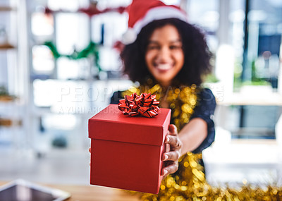 Buy stock photo Cropped shot of an unrecognizable businesswoman sitting alone in the office and holding out a christmas present