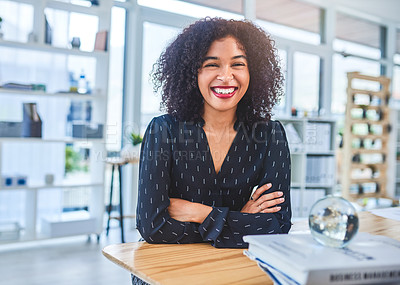 Buy stock photo Cropped portrait of an attractive young businesswoman sitting alone in her office with her arms folded