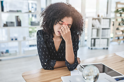 Buy stock photo Cropped shot of an attractive young businesswoman sitting alone in her office and suffering from a headache