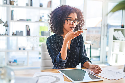 Buy stock photo Cropped shot of an attractive young businesswoman sitting alone in the office and sending voice notes on her cellphone