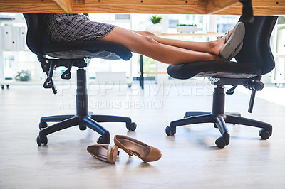 Buy stock photo Cropped shot of an unrecognizable businesswoman sitting alone in her office with her feet up during a break