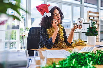 Buy stock photo Cropped shot of an attractive young businesswoman sitting and wearing christmas decorations while using her cellphone in the office