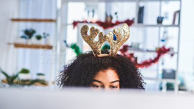 Buy stock photo Cropped shot of an attractive young businesswoman sitting alone in her office and using her computer while wearing christmas headgear