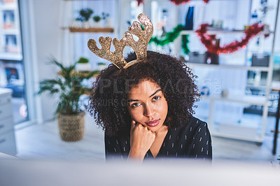 Buy stock photo Cropped portrait of an attractive young businesswoman sitting alone in her office and using her computer while wearing christmas headgear