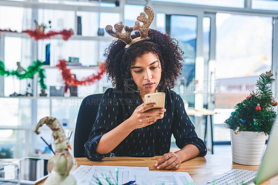 Buy stock photo Cropped shot of an attractive young customer service agent wearing christmas decorations in the office while using her cellphone