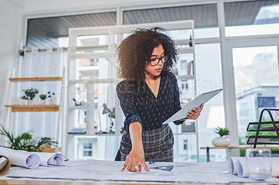 Buy stock photo Shot of a young businesswoman using a digital tablet while working with blueprints in an office