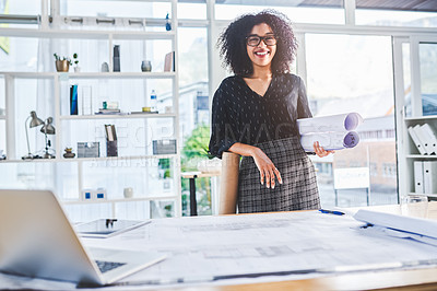Buy stock photo Portrait of a young businesswoman working with blueprints in an office