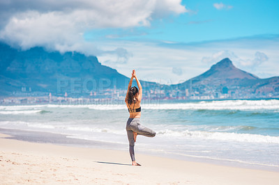 Buy stock photo Rearview shot of a young woman practising yoga at the beach