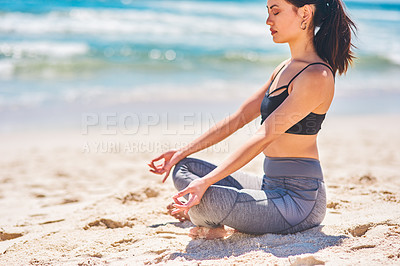 Buy stock photo Shot of a young woman meditating at the beach