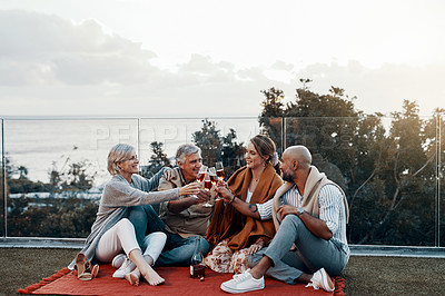 Buy stock photo Full length shot of an affectionate family making a toast with their wineglasses while celebrating a new year outdoors