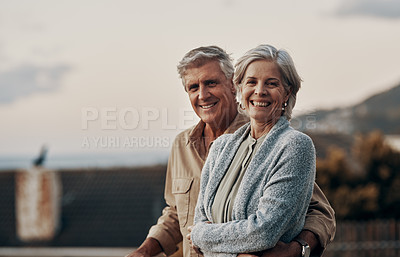 Buy stock photo Cropped portrait of an affectionate mature couple smiling while standing on a balcony outdoors