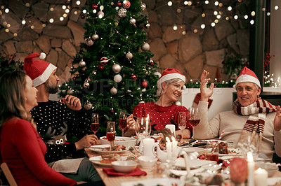 Buy stock photo Cropped shot of a cheerful family having dinner together on Christmas eve at home