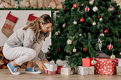 Buy stock photo Cropped shot of a carefree woman placing decorations on a Christmas tree inside at home during the day