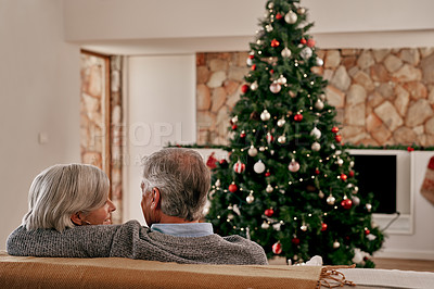 Buy stock photo Rearview shot of an unrecognizable mature couple seated together on a sofa holding each other while looking at a Christmas tree at home