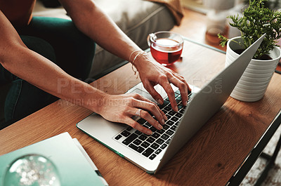 Buy stock photo Cropped shot of an unrecognizable woman using her laptop at home