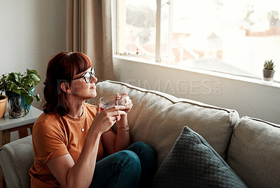 Buy stock photo Shot of a young woman enjoying a cup of tea while relaxing at home