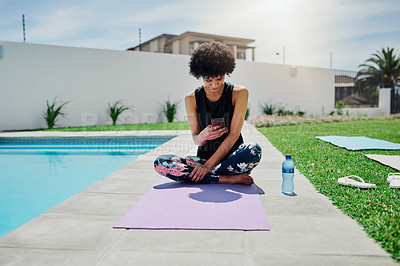 Buy stock photo Shot of a young woman using a smartphone while doing yoga in her backyard