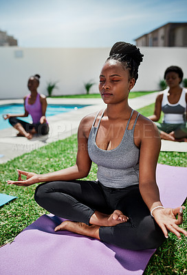 Buy stock photo Shot of a group of young women meditating together in a garden