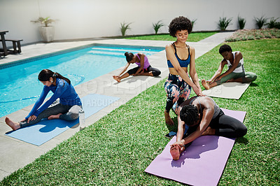 Buy stock photo Shot of a young woman being assisted by a yoga instructor in a garden