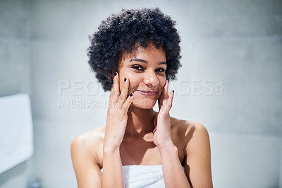 Buy stock photo Portrait of a confident young woman standing in front of a mirror while touching her face inside of a bathroom during the morning hours