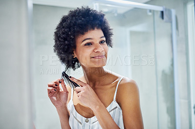 Buy stock photo Cropped shot of a cheerful young woman combing her hair while looking into a mirror inside of a bathroom during the morning hours