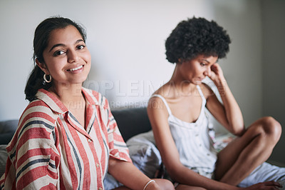 Buy stock photo Cropped portrait of two attractive young roommates sitting on the bed together during a study session at home