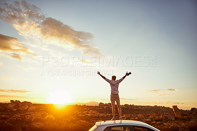 Buy stock photo Rearview shot of a young man standing on top of a car with his arms outstretched in a rural landscape