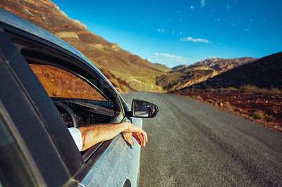 Buy stock photo Rearview shot of an unrecognisable man driving on a road in a rural landscape