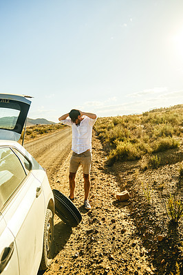 Buy stock photo Shot of a young man looking frustrated because of a flat tyre on his car in a rural area
