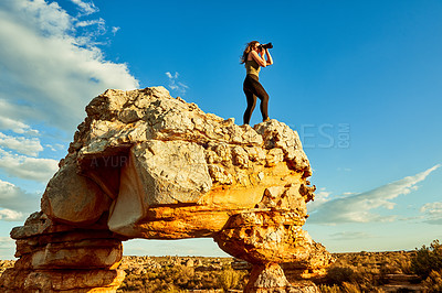 Buy stock photo Shot of a young woman taking photos while standing on a cliff in a rural landscape