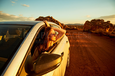 Buy stock photo Shot of a young woman looking out the window in a car while on a road trip