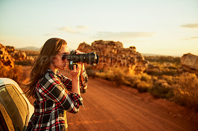 Buy stock photo Shot of a young woman taking photos while on a road trip in a rural landscape