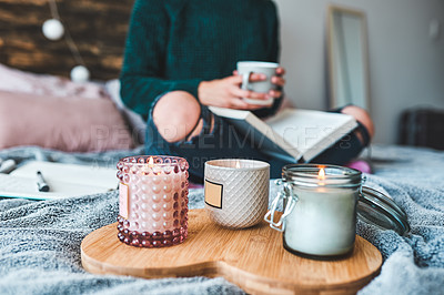 Buy stock photo Cropped shot of an unrecognizable young woman relaxing with a book and a cup of coffee on her bed at home