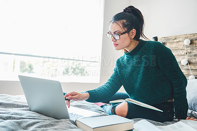 Buy stock photo Full length shot of an attractive young woman using a laptop to study while sitting on her bed