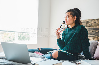 Buy stock photo Full length shot of an attractive young woman looking thoughtful while using a laptop to study on her bed