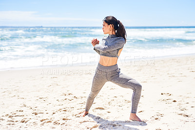 Buy stock photo Shot of a fit young woman warming up during a workout at the beach