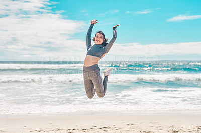 Buy stock photo Shot of a fit young woman jumping for joy during a workout at the beach