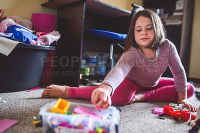 Buy stock photo Shot of a young girl playing with her toys at home