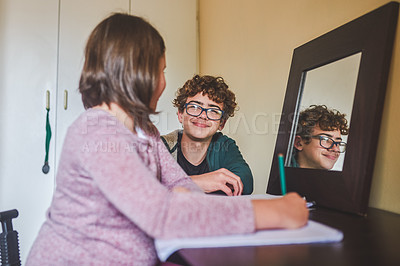 Buy stock photo Shot of a teenage boy sitting with his younger sister while she does her homework