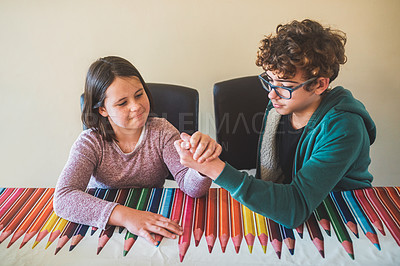 Buy stock photo Cropped shot of a teenage boy and his younger sister arm wrestling at home