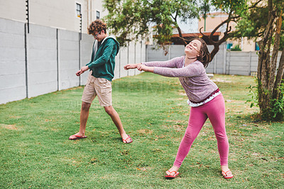 Buy stock photo Shot of a young girl and her older brother playing together outside