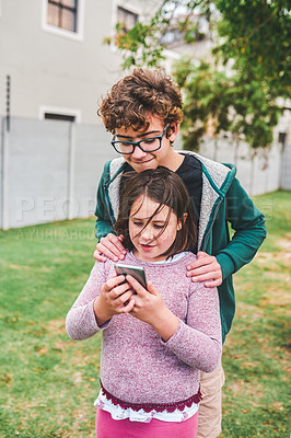 Buy stock photo Shot of a young girl and her older brother looking at something on a cellphone together