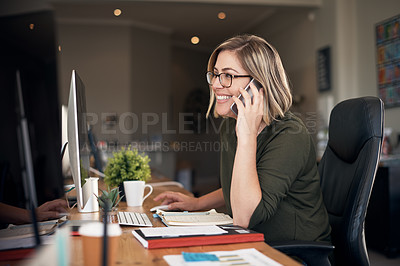 Buy stock photo Shot of a young businesswoman using a computer and smartphone in a modern office