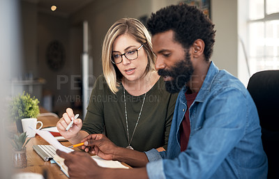 Buy stock photo Shot of a young businessman and businesswoman going through paperwork together in a modern office