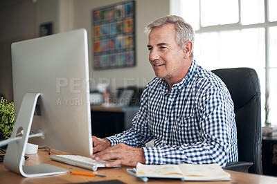 Buy stock photo Shot of a mature businessman using a computer in a modern office