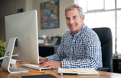 Buy stock photo Portrait of a mature businessman using a computer in a modern office