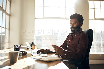 Buy stock photo Shot of a young businessman using a laptop while going through paperwork in an office
